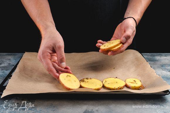 Противень выстелите пергаментом, выложите на него кружочки картофеля. Запекайте в заранее разогретой до 200°С духовке 15 минут.