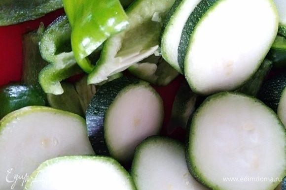 Молодые цукини вымыть и нарезать колечками толщиной около 0,5–0,7 см. Перец почистить и нарезать кусочками. Если взять перец желтый, то салат будет наряднее. Посолить и присыпать смесью перца. Сбрызнуть растительным маслом.