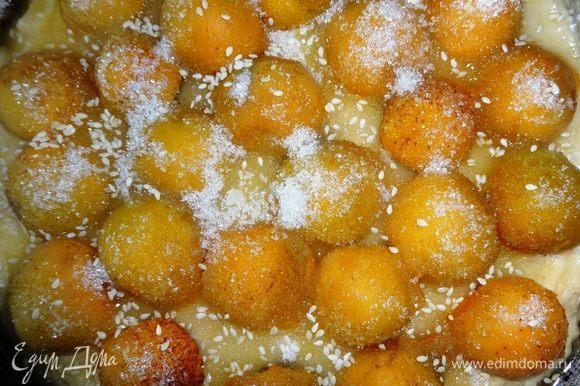 Пространство между абрикосами посыпать сахаром. Сливочное масло растопить и полить им поверх сахара и абрикосов. Посыпать весь пирог кунжутом. Поставить форму с пирогом в духовку, разогретую до 180°C и выпекать 30–35 минут. Готовый пирог аккуратно вынуть из формы и выложить на блюдо.