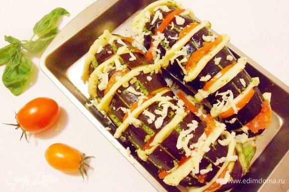 Твердые помидоры нарезать полукольцами, сыр — дольками такого же размера. Оставшийся сыр натереть на терке. Заполнить поперечные надрезы сыром и помидорами. Сверху посыпать тертым сыром.