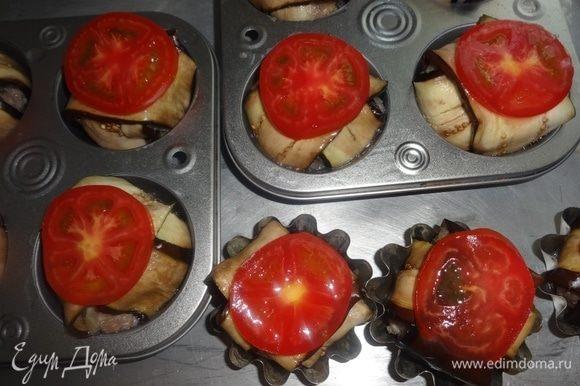 Смазать баклажаны в формочках остатками яйца и выложить на них кружки помидоров.