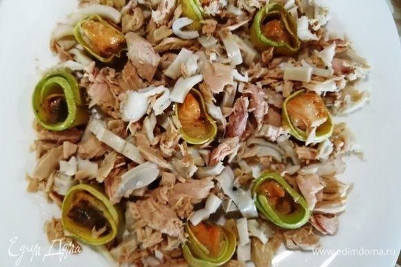 Собираем салат. На большую плоскую тарелку ставим рулетики из кабачка и форели. Выкладываем тунец с кальмарами.