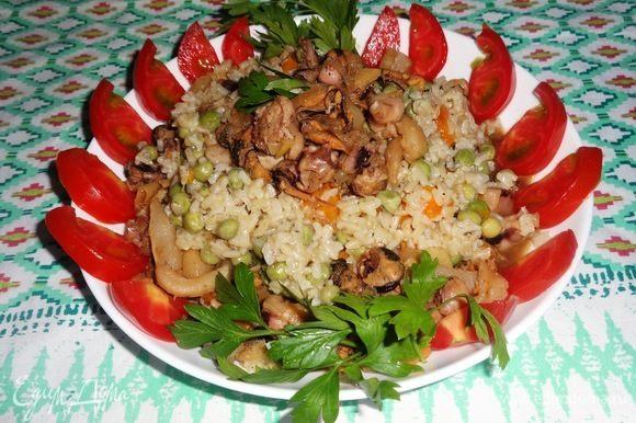 В тарелку выложить рис с овощами небольшой горкой. Вокруг него и сверху разложить морской коктейль. Украсить свежими овощами и зеленью. Блюдо вкусно и в горячем, и в холодном виде. Угощайтесь! Приятного аппетита!