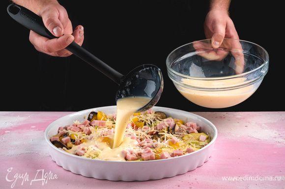 В форму выложите овощи, добавьте ветчину и натертый сыр, сверху вылейте яично-молочную массу.