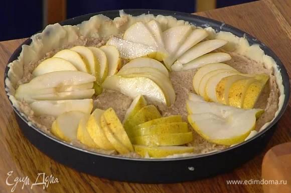 В форму с подмороженным тестом равномерно выложить марципановую пасту, сверху разложить груши.
