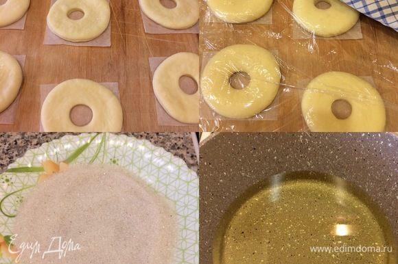 Заготовки пончиков накрыть и оставить в теплом месте на 30–40 минут. В миске смешать сахар и корицу для посыпки (сахар лучше брать мелкий). Спустя указанное время, в сотейник налить масло и хорошо подогреть.