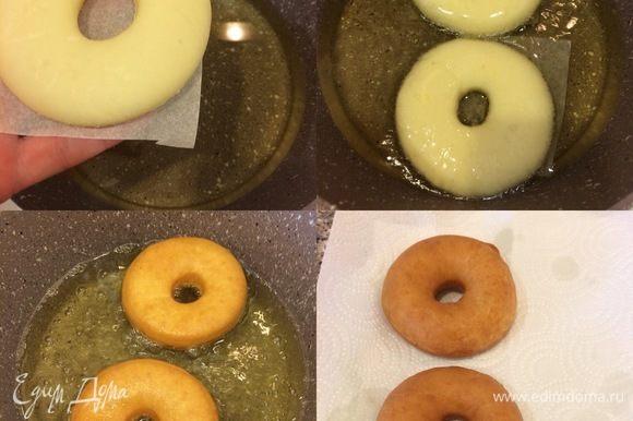 Опускать пончики аккуратно в горячее масло (вместе с бумагой) и через 3–4 секунды убрать бумагу. Переворачивая, жарить до готовности. Готовые пончики сложить на бумажное полотенце, дать слегка остыть 2–3 минуты.