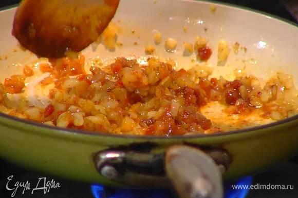 Разогреть в сковороде оливковое масло и слегка обжарить лук и чеснок, всыпать шафран, кориандр, хмели-сунели, уцхо-сунели, часть сванской соли и еще немного обжарить, затем добавить аджику, все перемешать и снять с огня.