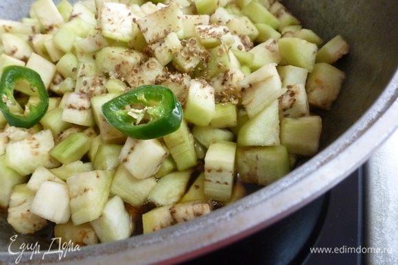 Выкладываем слегка отжатые от влаги баклажаны, всыпаем кориандр и чили (по вкусу).