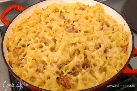 Сыр натереть на крупной терке, посыпать макароны с грибами и отправить в разогретую духовку на 15–20 минут.