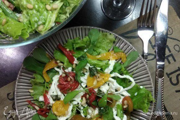Собираем салат. Если порционно: на микс из салатных листьев и руколы выкладываем в хаотичном порядке полоски перца, нити страчателлы, поливаем заправкой и посыпаем кедровыми орешками. Либо подаем в большом салатнике, перемешав все ингредиенты. Приятного аппетита!