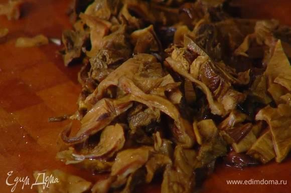 Сухие грибы залить горячей водой и дать постоять, затем отжать, сохранив воду, и порезать не очень мелко.