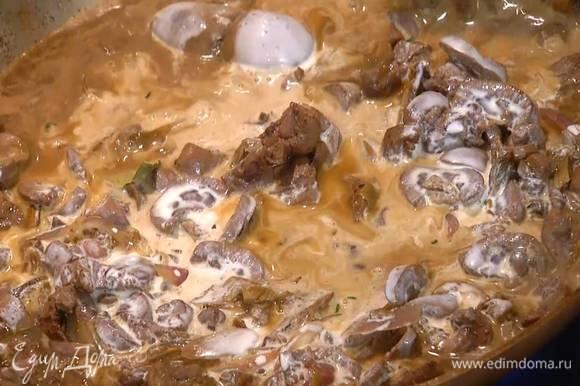 Вернуть почки в сковороду к луку и грибам, через сито влить воду, в которой замачивались грибы, дать жидкости немного выпариться, затем влить сливки, все перемешать и слегка все прогреть.