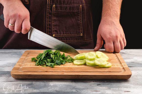 При необходимости порвите листья салата. Удалите кожуру с огурцов и нашинкуйте тонкими кольцами. Порубите мелко зелень.