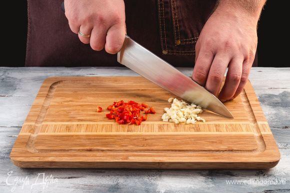 Измельчите чеснок и острый перец.