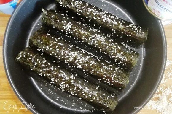 Выкладываем роллы на противень, смазываем маслом, оставшимся от филе тунца, и посыпаем кунжутом.