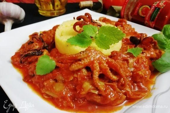 В центр большой тарелки выкладываем поленту, вокруг нее — осьминогов в соусе.