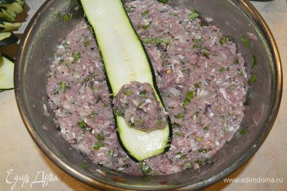 Включить духовку на 200°C. Распределить фарш на кончике цукини и свернуть цукини в рулетик.