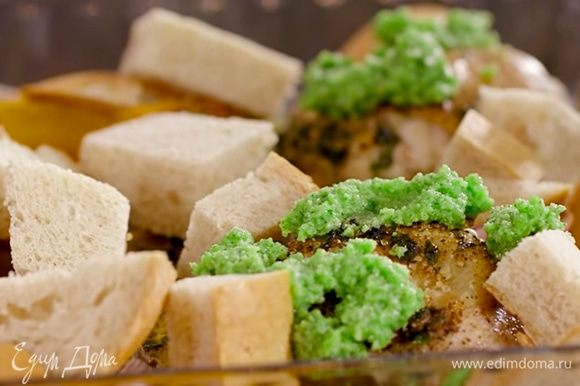 За 2–3 минуты до готовности взять 3 больших ломтя белого хлеба, нарезать их крупными кусками и добавить на противень. На бедра выложить ложкой часть соуса песто. Сверху полить все небольшим количеством оливкового масла и отправить обратно в духовку на пару минут.
