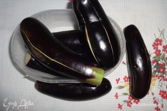 Баклажаны помыть, обсушить бумажным полотенцем. Отрезать плодоножки. Сделать в баклажанах продольные разрезы глубиной примерно 2 см на расстоянии 2,5–3 см друг от друга. До кончиков баклажанов разрезы не доводить, чтобы плоды не развалились.