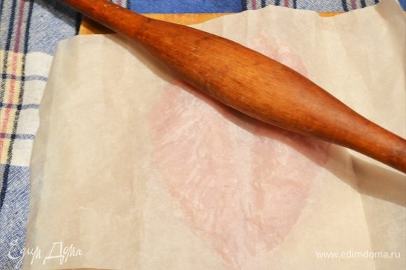 Накрываем грудку вторым листом пергамента. Берем скалку и начинаем как бы раскатывать филе осторожно, делая его равномерным по толщине.