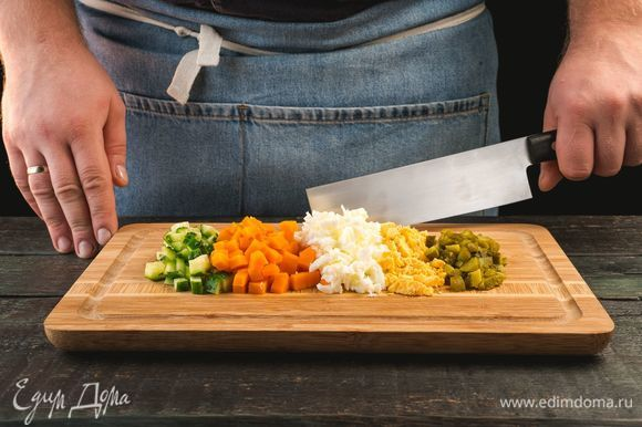 Отварите морковь и куриные яйца. Измельчите свежие и консервированные огурцы, вареные яйца, морковь.