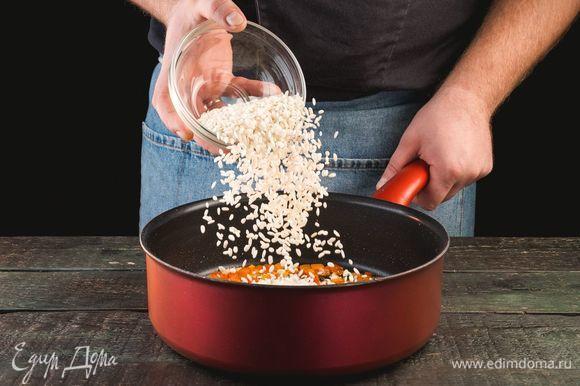 Добавьте к овощам рис и обжаривайте все вместе еще пару минут.