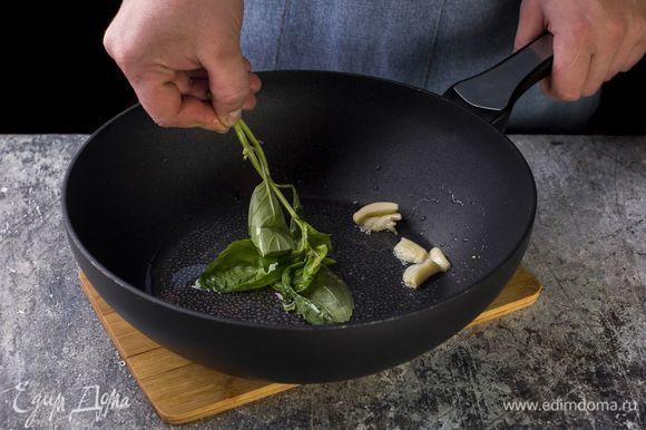 Приготовьте томатный соус: в сковороду налейте оливковое масло, слегка подогрейте, обжарьте раздавленный чеснок и базилик.