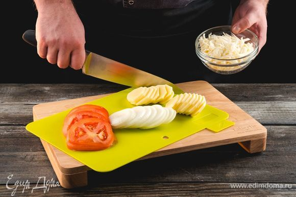 Нарежьте полукольцами лук, картофель, помидоры. Натрите сыр.