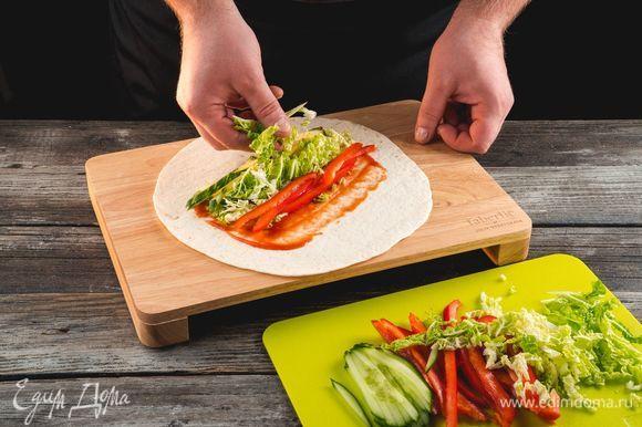 Смажьте тонкий лаваш томатным соусом. Выложите поверх соуса капусту, соломку из огурца и сладкого перца.