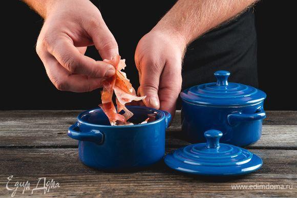 Выложите в кокотницу хамон и приправьте перцем.
