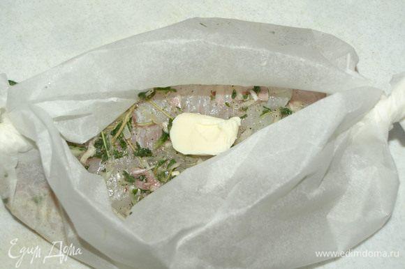Заворачиваем пергамент лодочкой и кладем на рыбу сливочное масло (0,5 ч. л.).