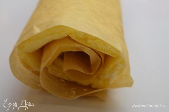 Вытащить готовый бисквит и перевернуть на бумагу, припыленную кукурузным крахмалом. Бумагу, на которой выпекался бисквит, аккуратно снять. Свернуть бисквит в рулет прямо с бумагой и оставить остывать.