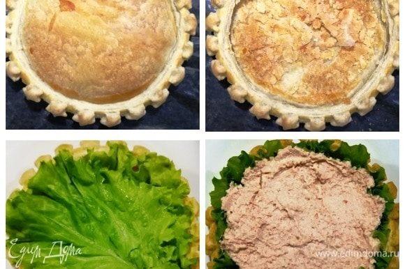 Собираем пирог. Центр остывшей выпечки приминаем ложкой. Выкладываем листья салата, поверх — начинку из рикотты и крабовых палочек.