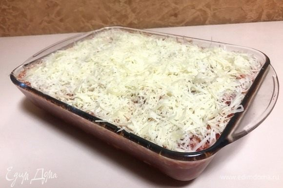 Посыпать блюдо тертым твердым сыром и поставить в разогретую до 200°C духовку на 45 минут.