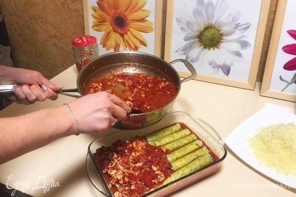 Смазать форму маслом и вылить 1/3 томатного соуса. Выложить фаршированные шпинатом и рикоттой каннеллони в форму для запекания сверху на соус. Желательно выкладывать трубочки в один слой, тогда они лучше пропитаются соусом и получатся вкуснее. Залить макаронные изделия оставшимся соусом.