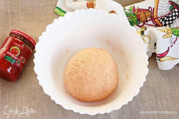 Муку пшеничную предварительно просеять. Всыпать сначала половину объема, вымешать, затем порционно добавить оставшуюся. Так как мука отличается по качеству, может потребоваться разное ее количество. Замесить крутое тесто. Добавить оливковое масло и месить, пока тесто не перестанет липнуть к рукам. Тесто станет эластичней. Укрыть миску с тестом пленкой и оставить в теплом месте для расстойки на 1,5–2 часа.