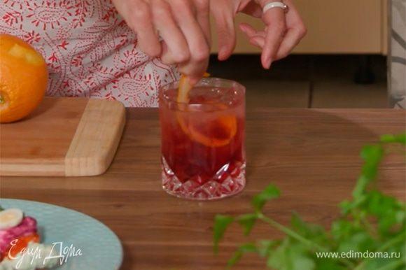 С апельсина двумя тонкими полосками срезать цедру, одну из них поместить в бокал с коктейлем, другую выжать в напиток.