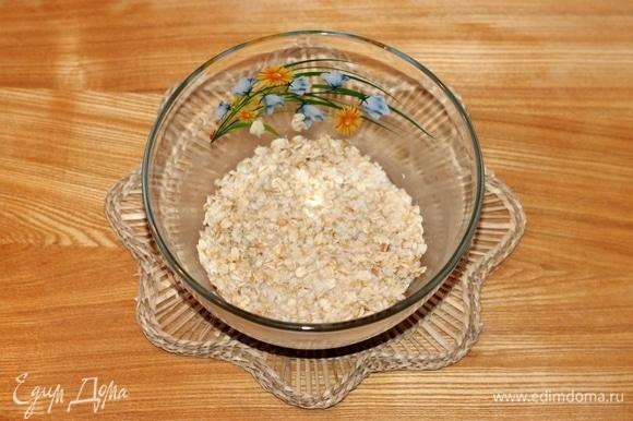Хлопья геркулеса (1 стакан = 240 мл) пересыпать в миску и залить горячей водой.