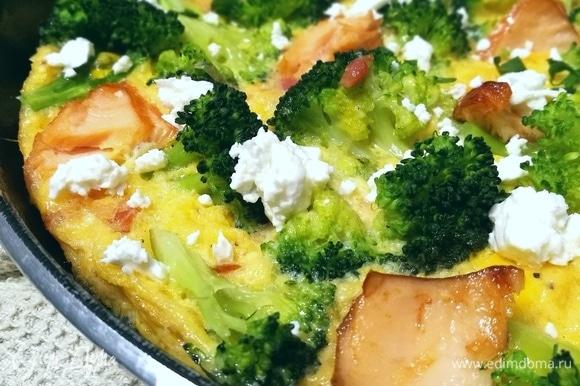 Горячую фриттату посыпать раскрошенной фетой и свежей зеленью.