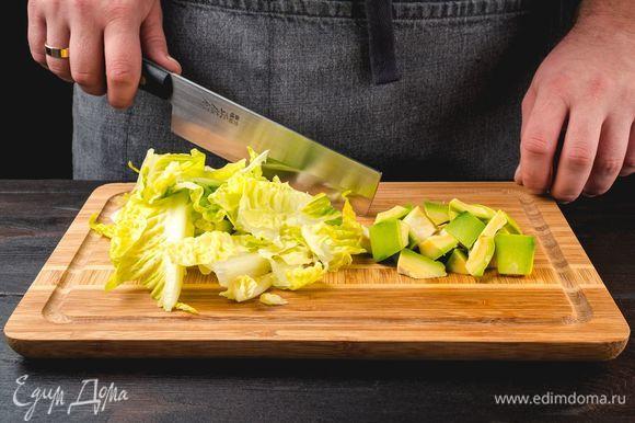 Мякоть авокадо и салатные листья нарежьте, сбрызните лимонным соком и перемешайте.
