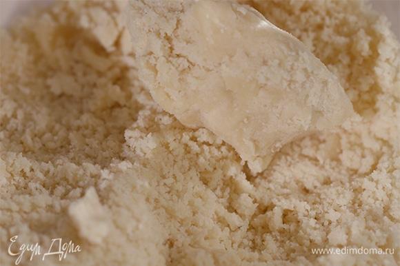 Пока варится суп, для печенья в блендере взбить муку, сливочное масло, щепотку соли и горчичного порошка. Добавить к получившейся крошке пармезан и чеддер, натертые на мелкой терке, и взбить на средней скорости до получения однородной массы.