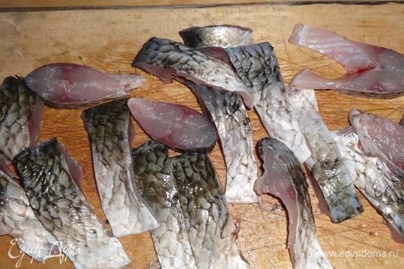 Нарезать тушки рыбы на мелкие кусочки, одновременно удаляя плавники.