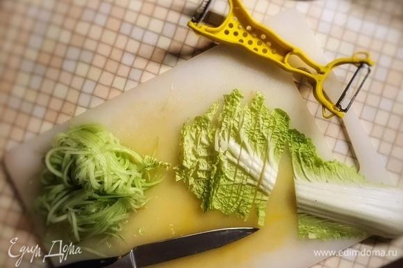 Очистите огурец от кожуры и нашинкуйте таким же способом, что и морковь, удалив при этом семенную часть. Листья салата нарежьте тонкими полосками. Красный лук тонко нарежьте кольцами или полукольцами. Выложите остальные овощи к моркови с перцем. Перемешайте и снимите с огня.