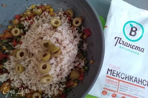 Всыпать рис и нарезанные оливки в сковороду, перемешать аккуратно. Полить лимонным соком и маслом. Попробовать на соль. Если нужно, посолить.