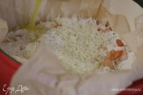 Тяжелый глубокий сотейник выстелить бумагой для выпечки, так чтобы края свешивались, влить четверть растопленного масла, равномерно выложить половину отваренного риса, сверху разложить обжаренные креветки с пряностями, а затем остальной рис, разровнять его и полить оставшимся маслом.