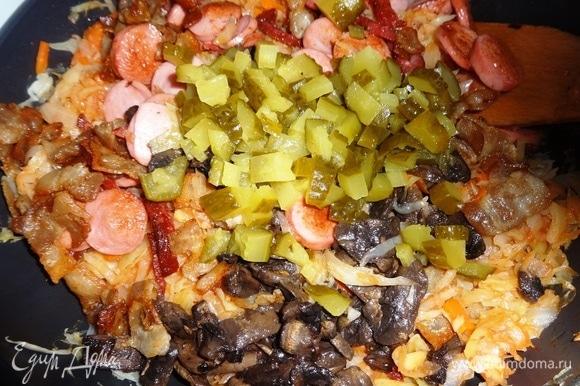 В сковороду с капустой добавить соленые огурцы, обжаренные сосиски, колбасу, бекон, грибы вместе с жиром, перемешать.