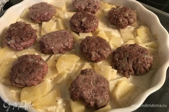 Снимаем фольгу с картошки, выкладываем поверх картофеля тефтели и запекаем еще 10 минут.