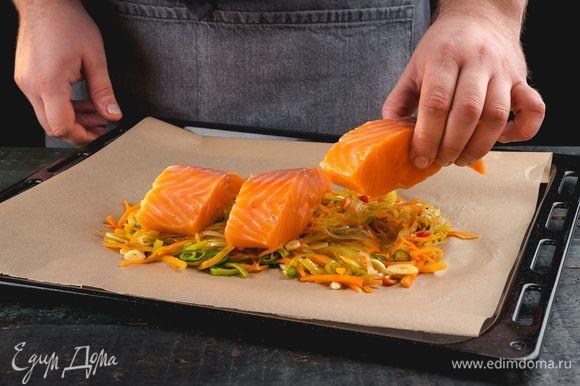 В небольшой глубокий противень выложите овощи со сковороды, сверху — филе лосося. Добавьте соль и перец по вкусу.