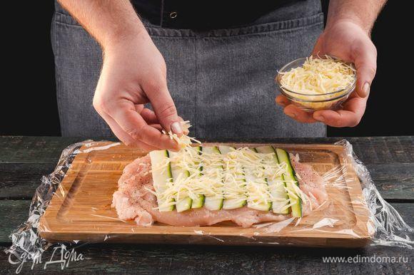 Куриное филе положите на пищевую пленку. На куриное филе выложите цукини. Посыпьте тертым сыром.